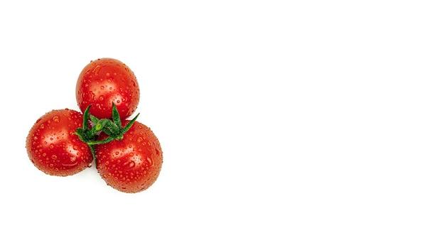 Trzy świeże pomidory czereśniowe z kroplami wody. widok z góry.