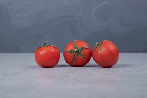 Trzy świeże pomidory na szarym tle. wysokiej jakości zdjęcie