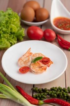 Trzy świeżej garneli i przyrodnich pomidorów w białym talerzu na drewnianym.