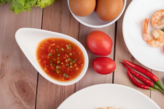 Trzy świeżej krewetki, jajka, chili, sos i pół pomidorów w białym talerzu na drewnianym.