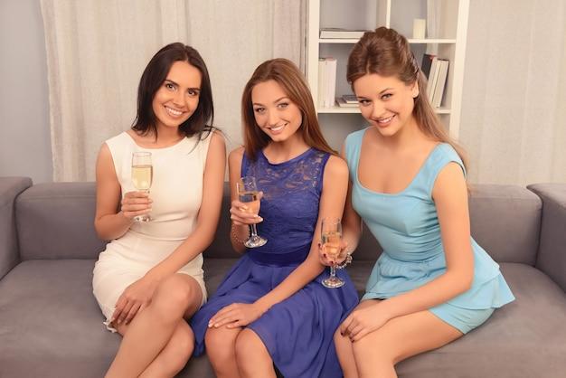 Trzy szczęśliwe dziewczyny glamour trzymając okulary z szampanem i uśmiechnięte