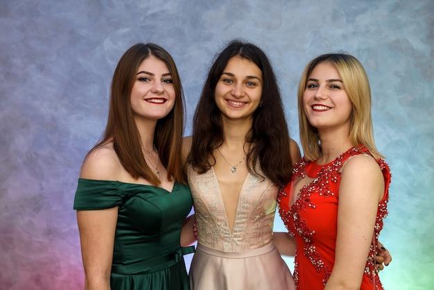 Trzy szczęśliwe dziewczyny w eleganckich sukienkach pozowanie na streszczenie tło. koncepcja uroczystości