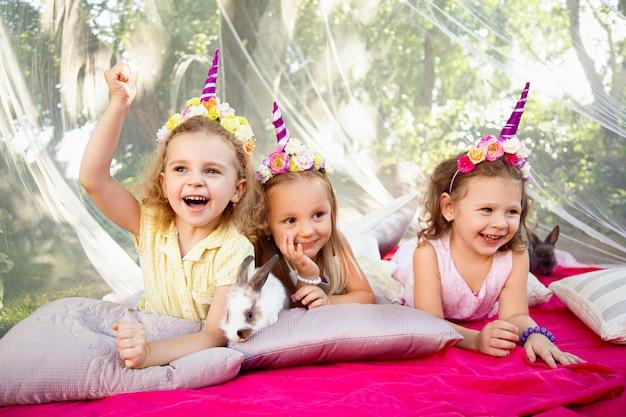 Trzy szczęśliwe dziewczyny w naturze z królikami
