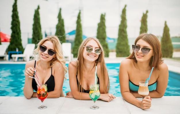Trzy szczęśliwe dziewczyny w strojach kąpielowych i okularach przeciwsłonecznych piją koktajle przy basenie. wakacje w kurorcie. opalone kobiety relaksują się w basenie