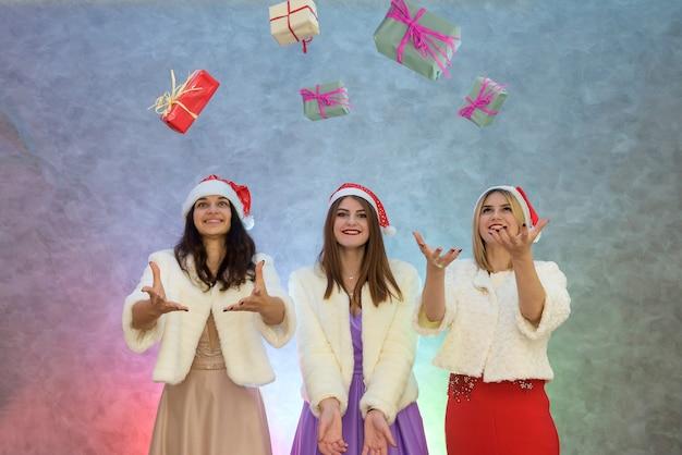 Trzy szczęśliwe dziewczyny wyrzucające swoje pudełka z prezentami. są w eleganckich sukienkach i futrzanych kurtkach