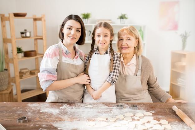 Trzy szczęśliwe gospodynie domowe w fartuchach stoją przy kuchennym stole z mąką i surowymi ciasteczkami, robiąc domowe ciasto