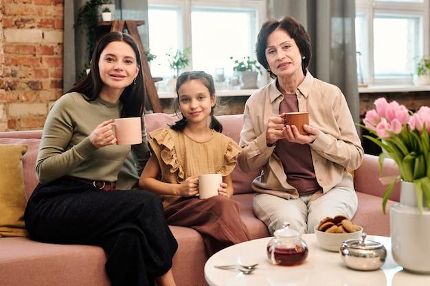 Trzy szczęśliwe kobiety pijące herbatę siedząc na kanapie przy serwowanym stole
