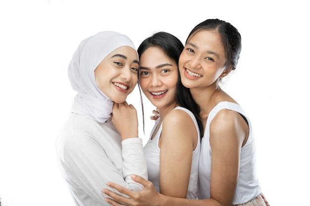 Trzy szczęśliwe ładne kobiety w białych ubraniach przytulają się