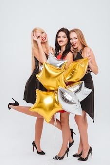 Trzy szczęśliwe, piękne młode kobiety stojące i bawiące się na białym tle