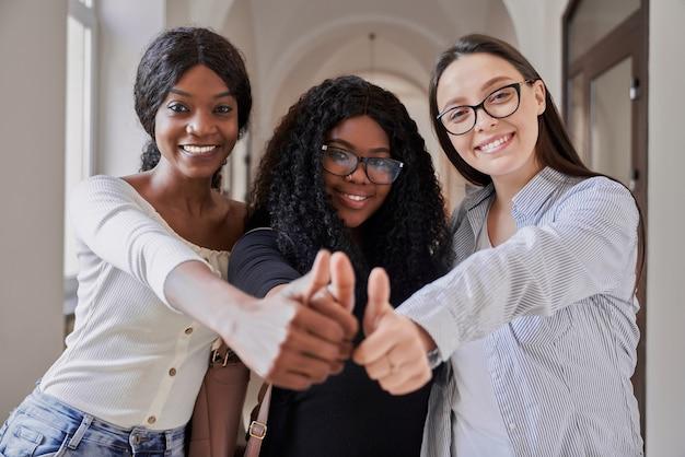 Trzy szczęśliwe studentki rasy mieszanej, uśmiechnięte, patrząc w kamerę i pokazujące super znak kciukami w górę na jasnym korytarzu uniwersyteckim. koncepcja znaczenia edukacji i studiowania w naszym życiu