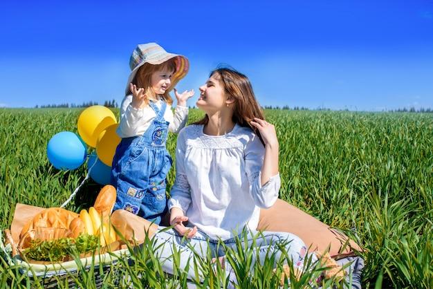 Trzy szczęśliwego dzieciaka siedzi na pinkinie na polu. błękitne niebo, zielona trawa. chleb, ciasta i owoce w koszu.