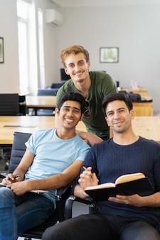 Trzy szczęśliwego kolegi uczą się studiowanie i patrzeje kamerę