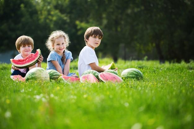 Trzy szczęśliwego uśmiechniętego dziecka łasowania arbuz w parku.