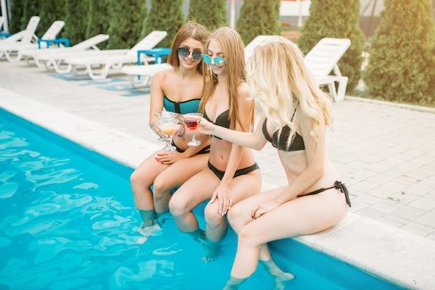 Trzy szczupłe dziewczyny w strojach kąpielowych i okularach przeciwsłonecznych piją koktajle na basenie. wakacje w kurorcie. opalone kobiety siedzące przy basenie