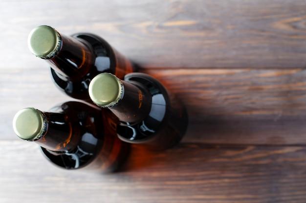 Trzy szklane butelki ciemnego piwa stoją na brązowym tle drewnianych. widok z góry. skopiuj miejsce.