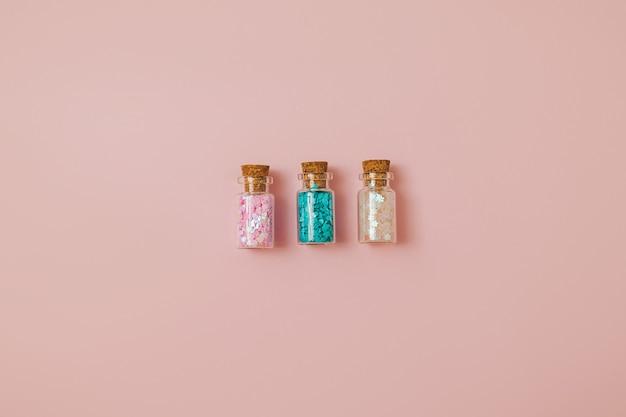 Trzy szklane butelki z różowymi i niebieskimi brokatowymi cekinami na pastelowym różowym tle. boże narodzenie, wakacje i party tło. skopiuj miejsce.