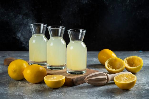 Trzy szklane dzbanki soku z cytryny na desce.