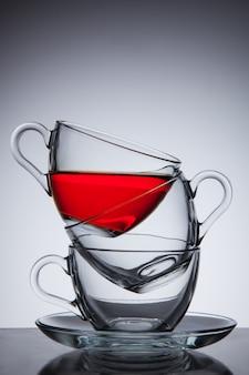 Trzy szklane filiżanki herbaty na spodku, dobry pomysł na pomysł, na szarym gradiencie.