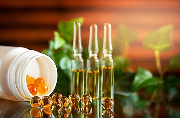 Trzy szklane przezroczyste ampułki do wstrzykiwań z żółtym lekiem w środku w tle biały słoik z żółtymi kapsułkami oleju rybiego drewniane tło zieloni szklana powierzchnia z odbiciem