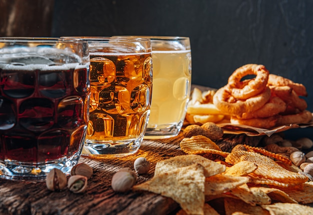 Trzy szklanki drogiego piwa rzemieślniczego, klasyczne, niefiltrowane i ciemne w szklance na stole z przekąską orzeszków ziemnych i pistacji oraz nachos