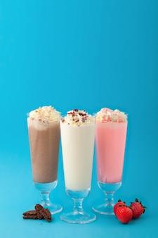 Trzy szklanki koktajli mlecznych, waniliowej truskawki czekolady na niebieskim tle