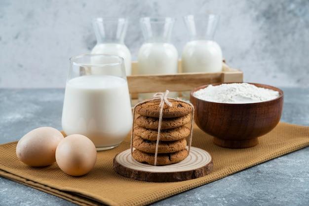 Trzy szklanki mleka z mąką i jajkami na szarym stole.