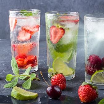 Trzy szklanki orzeźwiającego napoju detoksykującego z truskawkami, limonką, wiśnią i miętą na ciemnym tle.