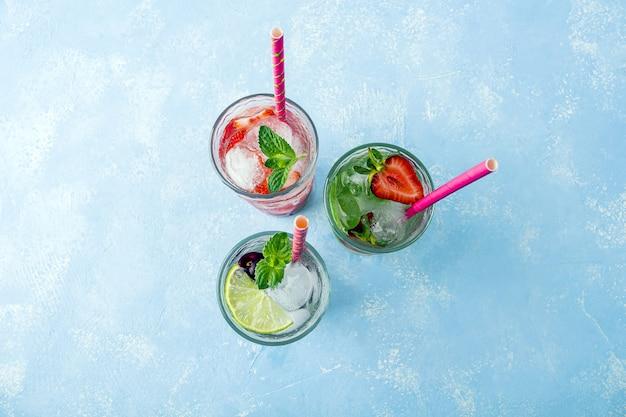 Trzy szklanki orzeźwiającego napoju detoksykującego z truskawkami, limonką, wiśnią i miętą na niebiesko