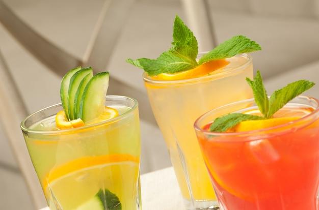 Trzy szklanki przezroczystego szkła z sokiem i cytryną na stole