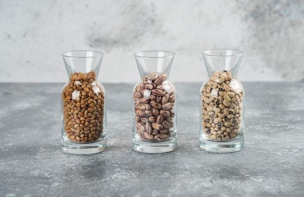 Trzy szklanki słoika z nieprzygotowaną fasolą na szarym stole.