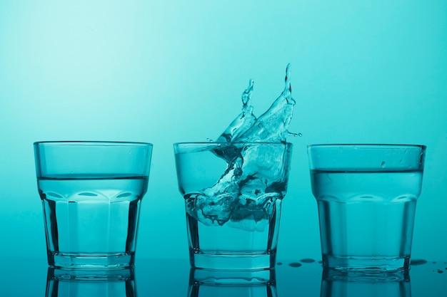 Trzy szklanki z czystą wodą i plamy na niebieskim tle