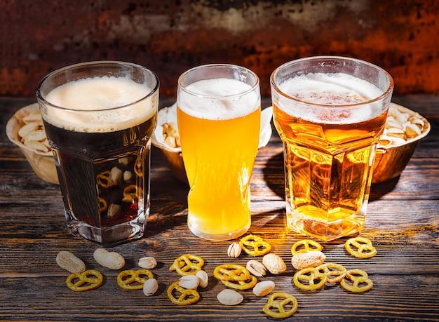 Trzy szklanki z jasnym, niefiltrowanym i ciemnym piwem obok talerzy z przekąskami, rozsypanymi małymi preclami i pistacjami na ciemnym drewnianym biurku. koncepcja żywności i napojów