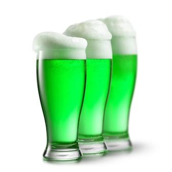 Trzy szklanki zielonego napoju alkoholowego z gęstą pianą. koncepcja happy st patrick's day.