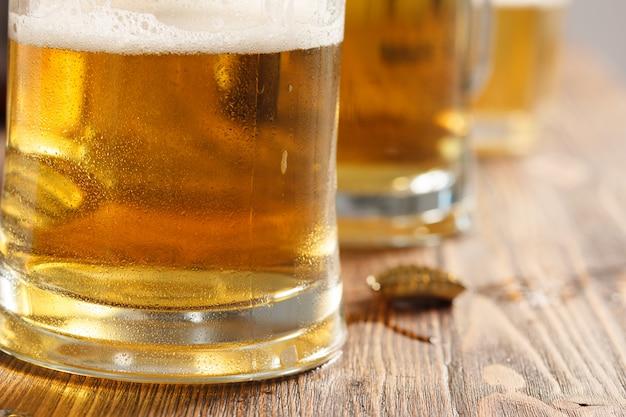 Trzy szklanki zimnego piwa na biurku w barze lub pubie