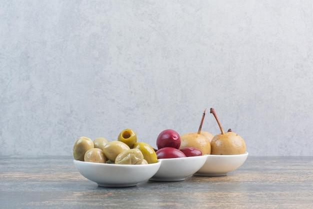 Trzy talerze oliwek i pyszne owoce na marmurowym tle. zdjęcie wysokiej jakości