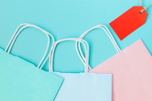 Trzy torby papierowe z czerwonym znacznikiem na niebieskim tle.