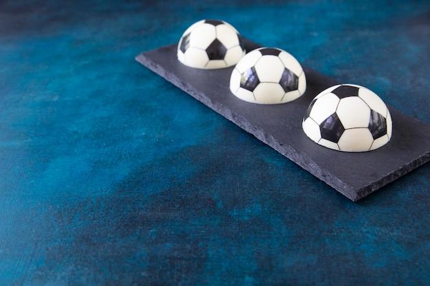 Trzy torty czekoladowe w kształcie piłek futbolowych na prostokątnej czarnej płycie w rogu z miejscem na kopię. kreatywny prezent dla fana europejskiej piłki nożnej
