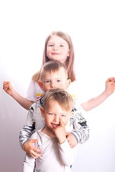 Trzy twarze szczęśliwych małych dzieci - jedna siostra i dwóch braci na białym tle na jasnobiałej powierzchni