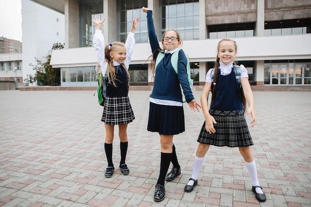 Trzy uczennice w mundurkach w spódniczkach i golfach cieszą się z zakończenia lekcji.
