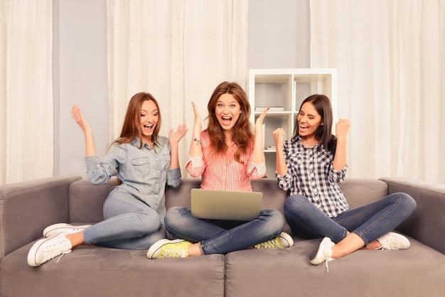 Trzy udane szczęśliwe dziewczyny siedzą na kanapie z laptopem