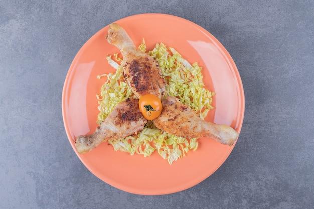 Trzy udka z kurczaka na pomarańczowym talerzu.