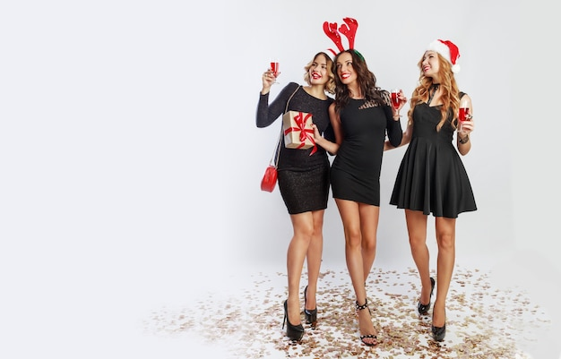 Trzy urocze dziewczyny spędzające czas na imprezie noworocznej. trzymając kieliszek szampana. noszenie kapeluszy maskaradowych.