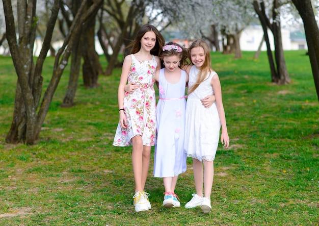 Trzy urocze dziewczyny w sukienkach trzymają się za ręce w kręgu, trzymając się za ręce. wiosna, ogród.