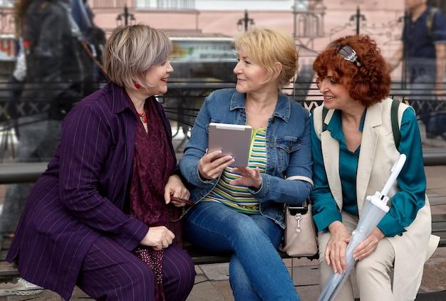 Trzy uśmiechnięte białe kobiety w wieku dojrzałym rozmawiają i omawiają informacje na ekranie komputera typu tablet.