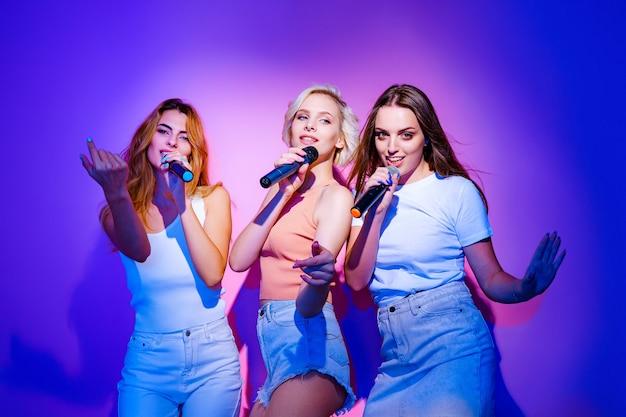 Trzy uśmiechnięte młode dziewczyny śpiewają piosenki w mikrofonie