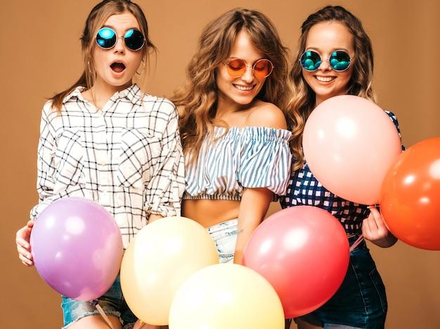 Trzy uśmiechnięte piękne kobiety w kraciaste koszule letnie ubrania. girls posing. modele z kolorowymi balonami w okularach przeciwsłonecznych. zabawy, gotowe na obchody urodzin