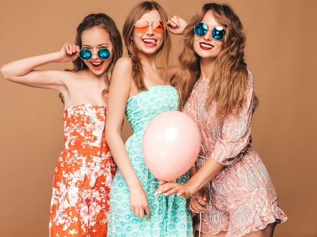 Trzy uśmiechnięte piękne kobiety w letnich sukienkach. girls posing. modele z kolorowymi balonami. zabawy, gotowe na uroczystości urodzinowe lub przyjęcie świąteczne