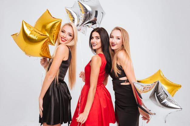 Trzy uśmiechnięte śliczne dziewczyny z balonami w kształcie gwiazdy stoją razem na białym tle