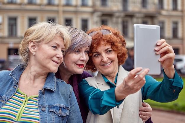 Trzy uśmiechnięte starsze kobiety rasy kaukaskiej robią selfie w centrum europejskiego miasta z tabletem.