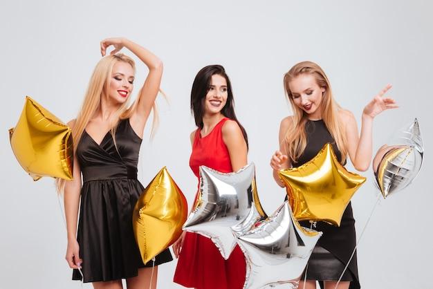 Trzy uśmiechnięte urocze młode kobiety z balonami w kształcie gwiazdy tańczą i bawią się na białym tle